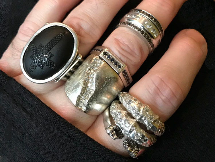 Image of gold men's designer rings stacked on hand.